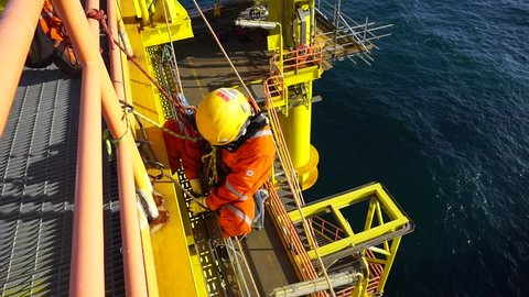 KELANTAN, MALAYSIA - JAN 10 2016 : Man working overboard. Abseiler complete with personal protective equipment (PPE) climbing and hanging at the edge of oil and gas rig platform in the middle of sea.