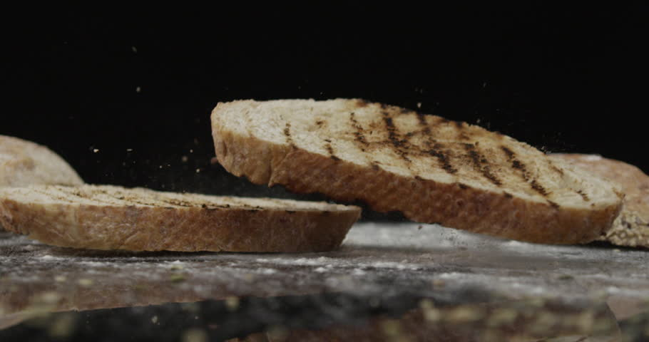 Slow motion. Two toasted slices of bread fall on a smooth table on black background.
