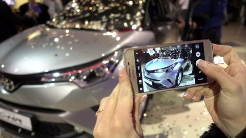 KHERSON, UKRAINE - DECEMBER 16, 2016: Woman Taking photo by Mobile Phone of New Toyota car presentation