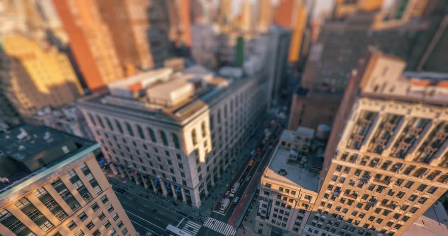 Aerial view of street intersection traffic in midtown Manhattan from above. New York City NYC, NY. 4K UHD timelapse, tilt shift lens blur.