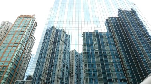 Low angle curtain wall reflection modern apartment building, high rise mansion construction, slide shot, camera move along street, looking upwards. Flat glass-walled bluish facade of modern tower