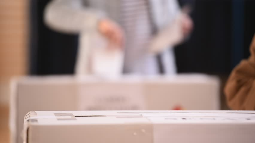 Unrecognizable people casting votes into the ballot box during elections | Shutterstock HD Video #22400050
