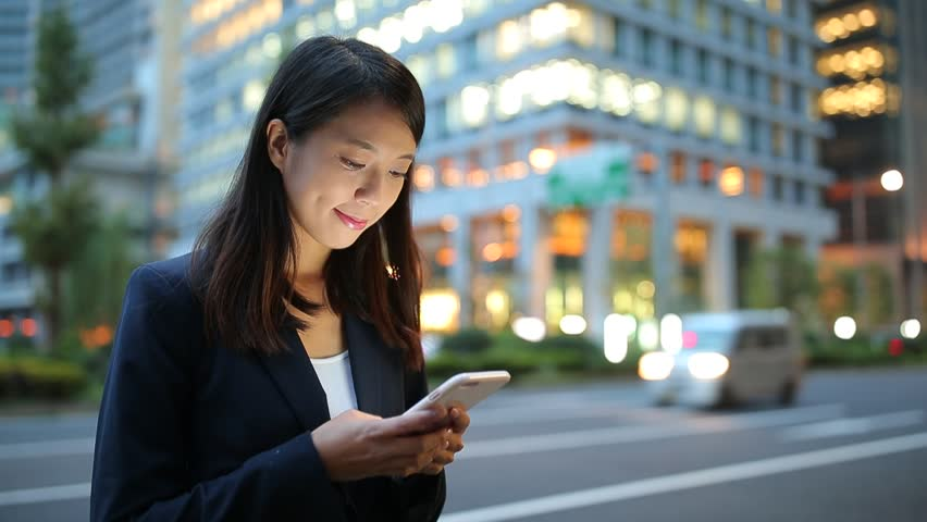 Businesswoman looking at mobile phone at evening | Shutterstock HD Video #22408024