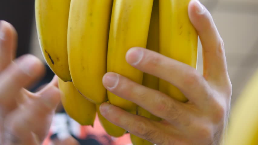 Male hand selecting bananas at the supermarket. Man taking a bunch of bananas from counter in a grocery store. Guy selecting fresh fruit at produce department of shop. Buyer chooses food. Close up | Shutterstock HD Video #22420030