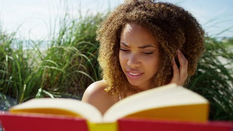 Portrait of beautiful voluptuous smiling Ethnic African American female on the beach for leisure reading a book RED DRAGON