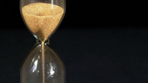 Hourglass on a black background, the sand falls inside. Close Up. Running Sand in the Sandglass. Egg timer emptying against a black background. Sands move through hour glass. Full HD 1920 x 1080p, 29