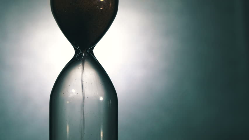 Hourglass on a White background, the sand falls inside. Close Up. Time Out. Running Sand in the Sandglass. Egg timer emptying against a White background. Sands move through hour glass. Ultra HD, 4K