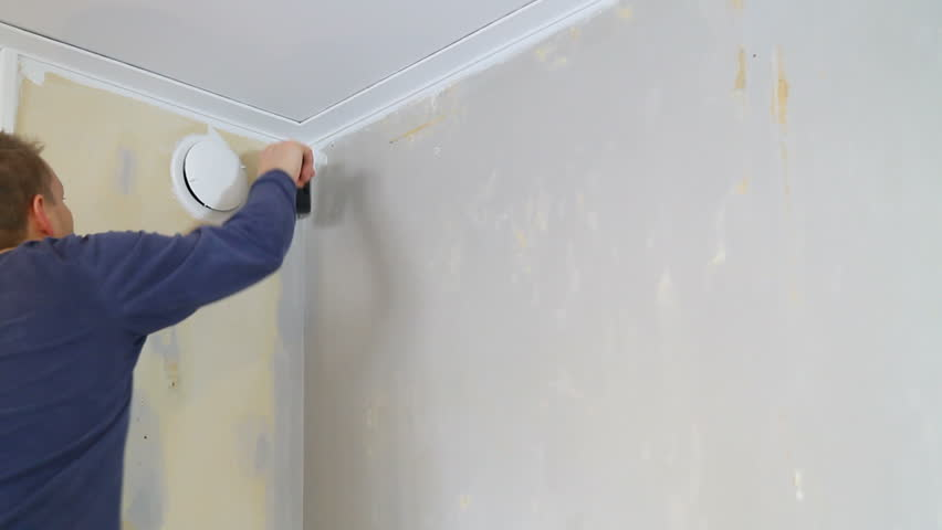 Applying wallpaper  glue using a large brush.