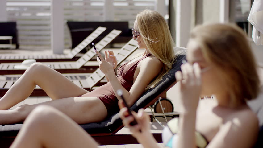 Young beautiful girls Relaxing with Phones in Deck Chair outdoor | Shutterstock HD Video #22448170