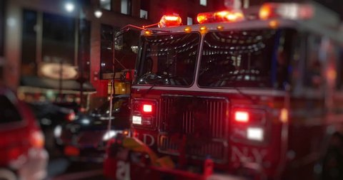 A fire truck with flashing red lights sits outside a Manhattan apartment building at night.