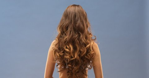 Gorgeous wavy hair flowing on her back close up, isolated on blue background