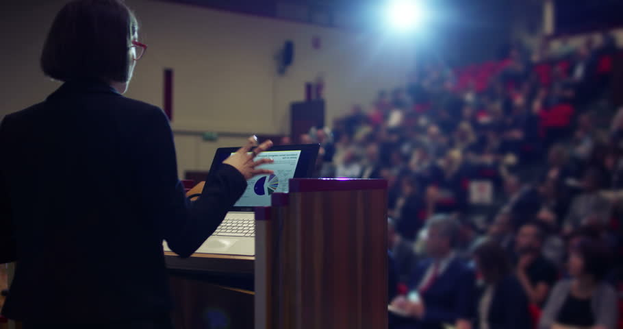 A woman holds a speech to the audience in an auditorium on a convention of economics and finance their business.concept: world economy, futuristic conference, holograms,future business world