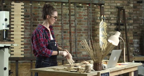 Hipster girl starts painting a wooden star in her lovely workshop. She's dressed in checkered shirt. She has a brick wall behind her/Young Pretty Hipster Girl Engaged in Handmade