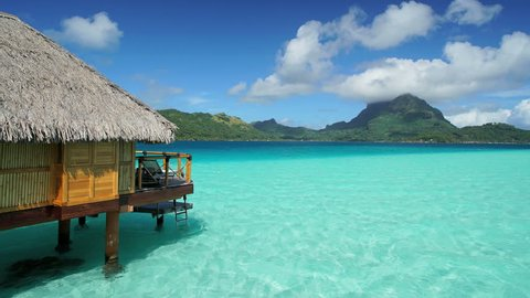 Time lapse view of aquamarine lagoon Overwater luxury Bungalows in tropical Tahitian vacation resort of Bora Bora Island in the South Pacific