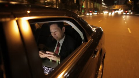 MH TS POV Businessman Riding in Back Seat of Car Talking on Phone at Night / Singapore