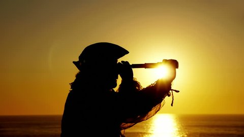Explorer With Spyglass Silhouette (HD). Explorer or sailor silhouette against sunset with a spyglass looking around.