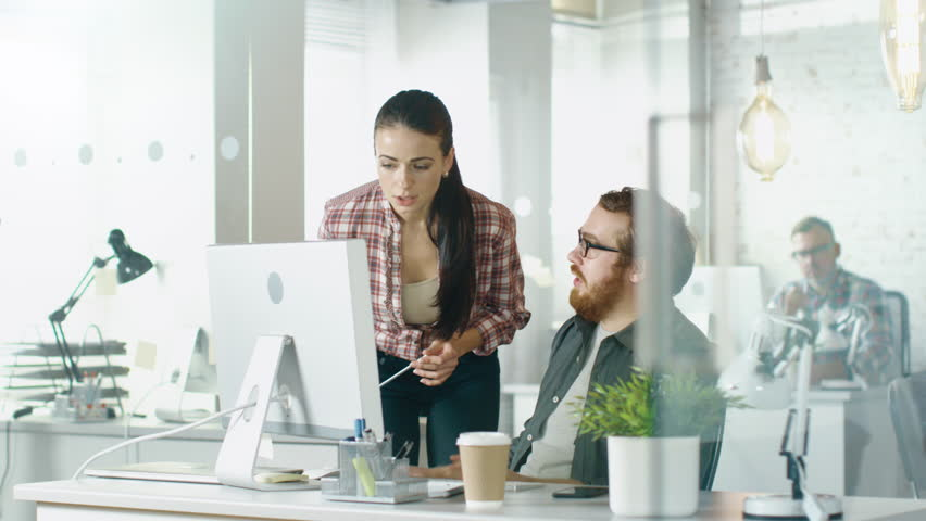 In a Busy Office Beautiful Girl Approaches Her Male Colleague Who is Sitting at His Desk and Points at Something on His Screen, they Discuss this Matter. Office is Modern. Shot on RED EPIC (uhd). | Shutterstock HD Video #22521049