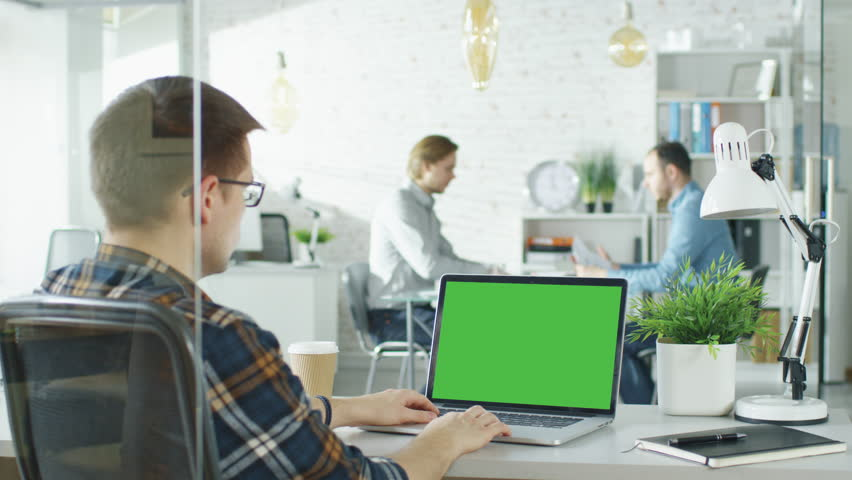 Close-up of a Man Sitting at His Desk with Green Screen Laptop. In Background Blurred and Brightly Lit Office where Two Young Man Shake Hands and Sit Down For Conversation. Shot on RED EPIC (uhd).