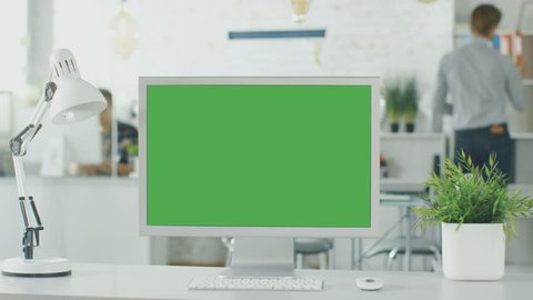 Close-up of a Green Screen on a Personal Computer. In Background Blurred and Brightly Lit Office where People go Through Office Routine. Shot on RED EPIC (uhd).