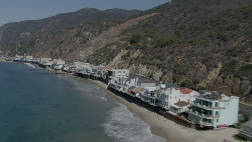 aerial flying shot of California coast, revealing beachfront homes at the base of the hillside circa 2009