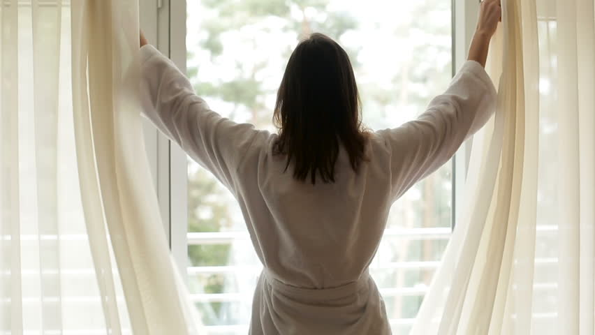Girl in a white robe comes out from the left side to the window and opens the curtains | Shutterstock HD Video #22531900