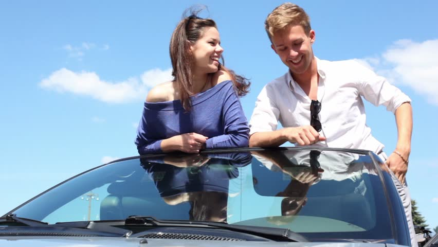 Young couple rest on front window of cabriolet and talk at sunny summer day