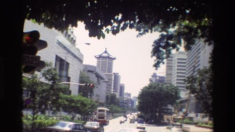 SINGAPORE 1984: people cross the street in a large city at a leisurely pace