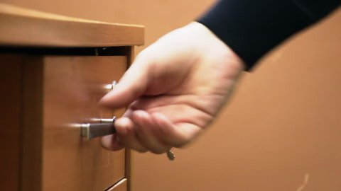 A man opens a locked Desk drawer. Puts it in the drawer business papers and closes the drawer.