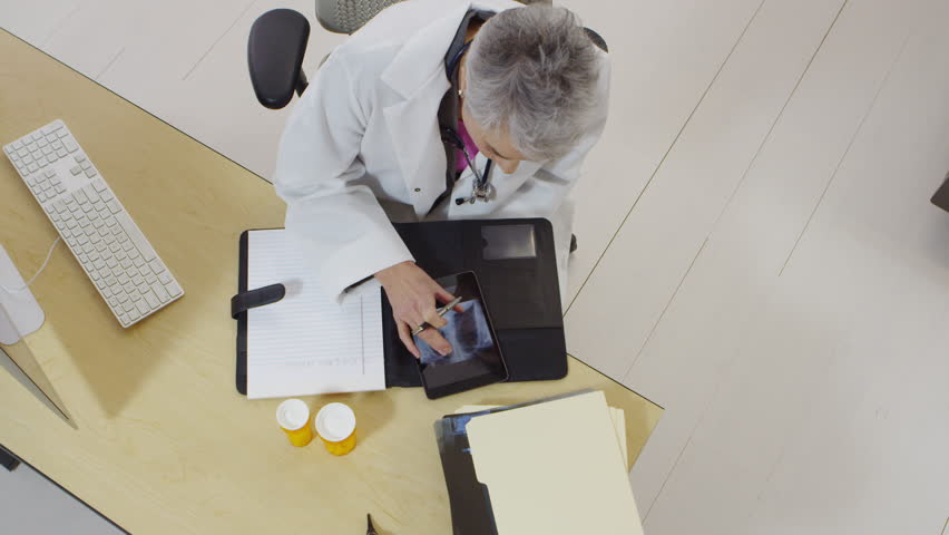 Top view of doctor looking at x-rays and taking notes on her tablet | Shutterstock HD Video #22640113