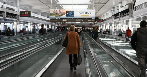 DENVER, COLORADO - DEC 2016: Denver International Airport passenger escalator POV. Busy airline hub with passengers on travel, vacation and business. 187 destinations and 20 international cities.