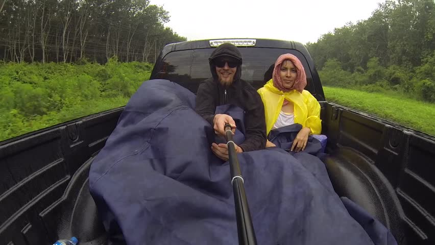 Young couple hitchhiking around the world and goes to the back of a truck in Thailand. GoPro funny selfie HD shot