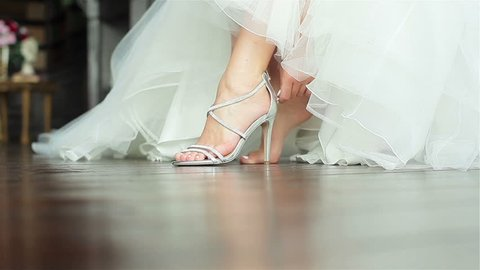 Woman puts on shoes hands close up shallow depth of field. Bride fastens zipper on luxurious high heeled sandals sitting in gorgeous white gown getting ready prepared for dancing at wedding ceremony