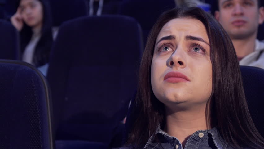 Pretty caucasian woman watching drama at the movie theater. Attractive brown haired girl having sad face at the cinema. Close up of female teenager worrying about film characters | Shutterstock HD Video #22709560
