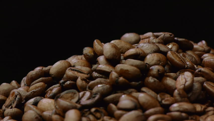 A pile of roasted coffee beans rotating on black background. Seamless loop.