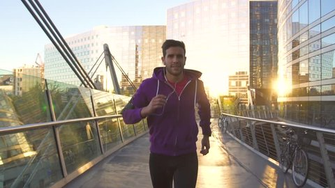 athlete with earphones running in the city, Slow motion movie