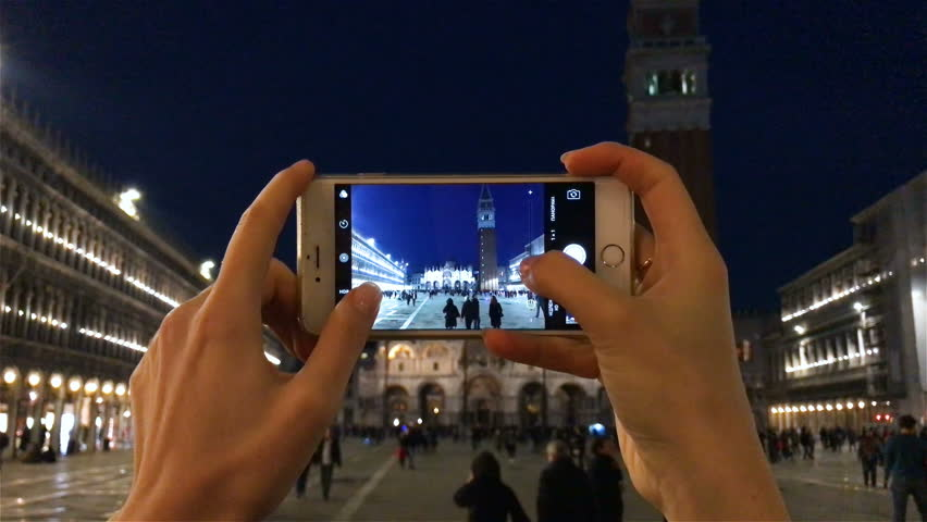 VENICE ITALY 25 NOV 2016: phone photo at night by smartphone mobile camera. Young woman taking picture background, shooting video, holding smart cell device by hands. Nightlife at San Marco, Venezia .