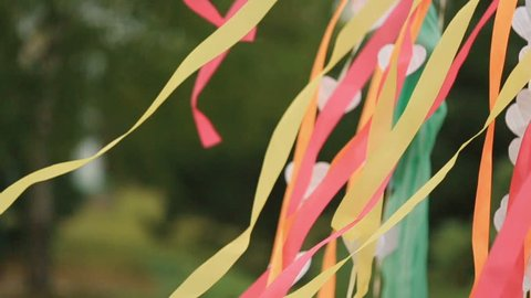Wind blows colorful ribbons and paper hearts hanging from wedding altar