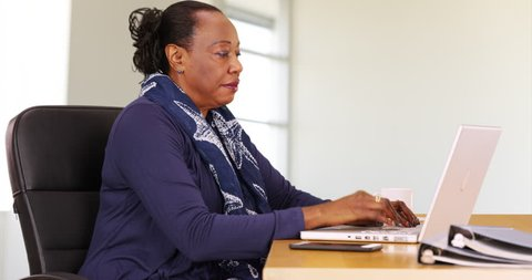A black businesswoman uses a laptop at her desk. An African American woman thinks about her work on her computer. 4k
