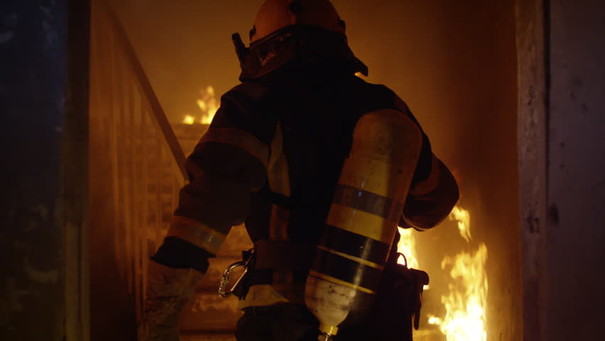 Brave Firefighter Runs Up The Stairs. In Slow Motion. Raging Fire is Seen Everywhere.  Shot on RED EPIC 4K (UHD).