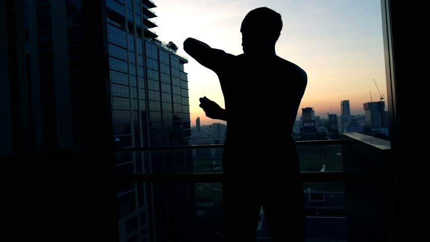Silhouette of man applying anti-perspirant on armpit on terrace, super slow motion 240fps