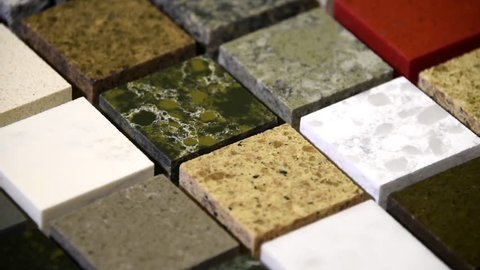 Floor tiles concept. Kitchen granite counter top color samples. Flooring tiles in different colors. Slow motion of granite, marble and quartz stone squares. Rock tiles rotating.