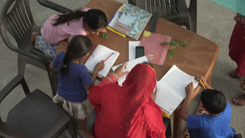 INDIA - CIRCA MAY 2016 - Indian mother helps and teaches children kids with school homework, India