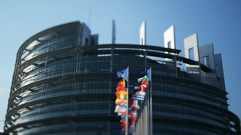 Impressive European Parliament building in Strasbourg, France with flags waving on a spring morning - real tilt-shift lens used to put the accents to the waving flags