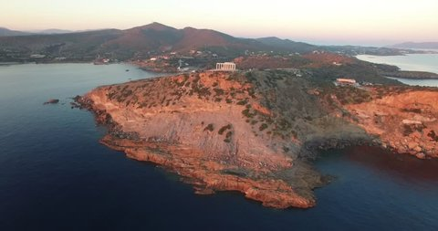 Drone flying from distance to the temple of Poseidon during sunset time in Athens