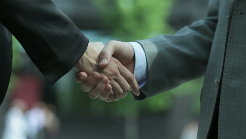 Close-up of two business people shaking hands to conclude the deal
