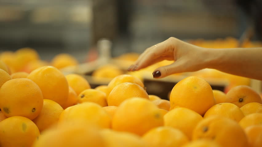 Woman chooses oranges at a supermarket. | Shutterstock HD Video #22892590