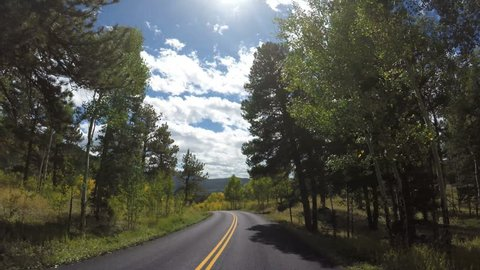 4K POV Point of view shot driving down tree lined curved mountain road with blue sky clouds on a fall day.