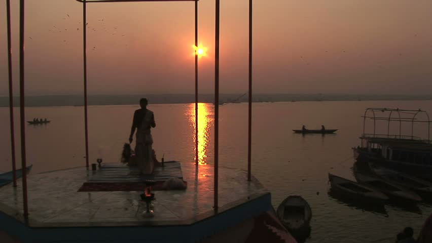 religious leader offering prayers with Ganges river and rising sun.Circa November, 2008, Veranasi, India