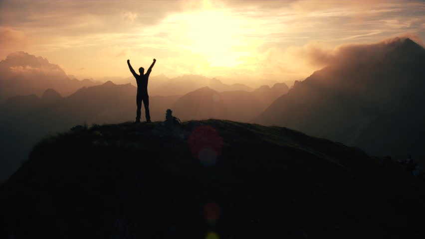 Aerial, edited - Moving above silhouette of a man standing on top of the mountain. Man raising arms victoriously after climbing the mountain | Shutterstock HD Video #22952920