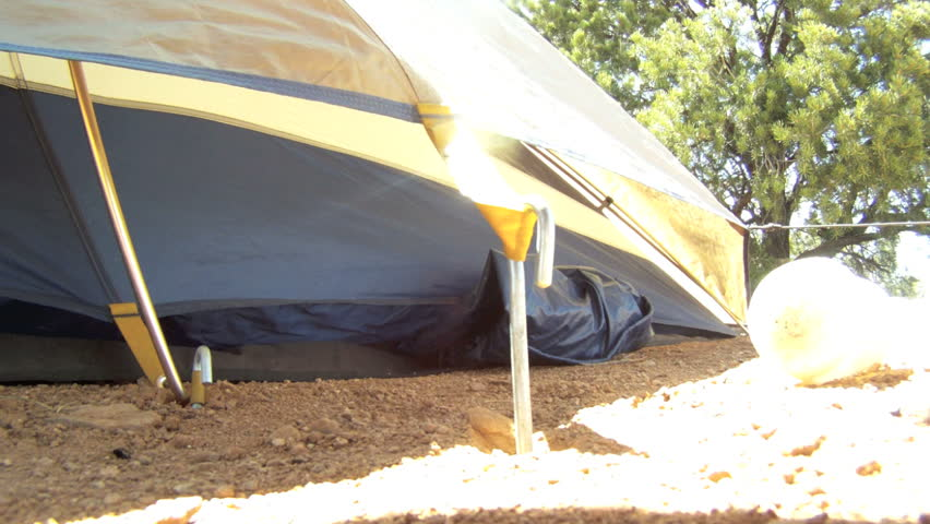 Camper Drives Tent Pegs With Mallet